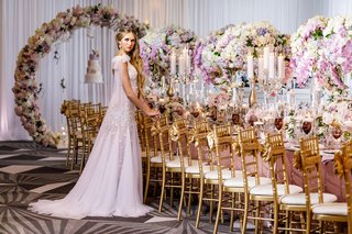 wedding-reception-gold-chairs-purple-pink-white-centerpieces-candles-bride-in-long-dress-godet-skirt
