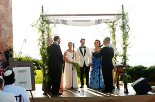 bride-and-groom-under-tallit-with-greenery-chuppah