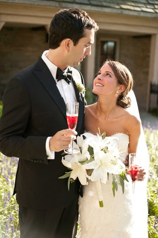 bride-and-groom-toast-at-their-wedding-with-white-lily-bouquet-flowers