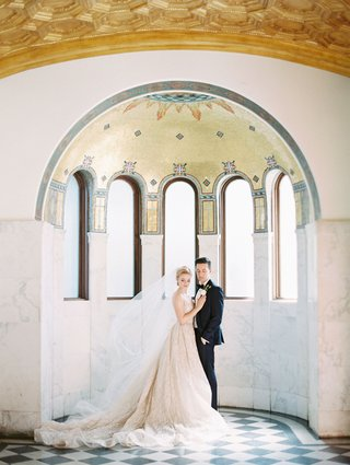 bride-and-groom-portrait-downtown-los-angeles-venue-vibiana-mosaic-arch-checkerboard-floor-lazaro