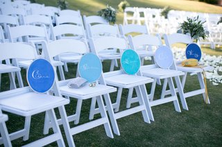 names-of-guests-placed-on-white-chairs-at-beach-wedding