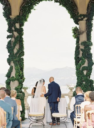 bride-and-groom-lake-como-wedding-ceremony-greenery-on-stone-pillar-archway-villa-del-balbianello