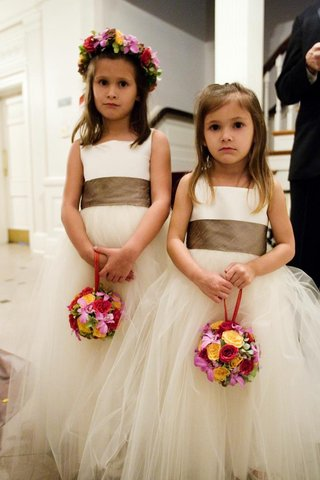 two-flower-girls-in-tulle-dresses-with-pomander-balls