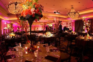 pink-lighting-in-reception-ballroom-with-large-flower-centerpieces