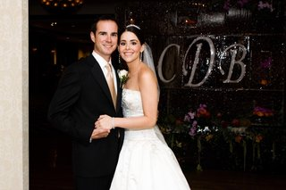 bride-and-groom-in-front-of-monogram-ice-sculpture