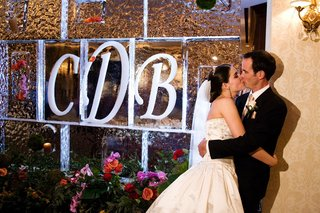 bride-and-groom-kiss-in-front-of-ice-sculpture-wall