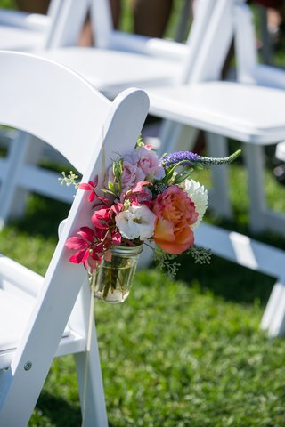 pink-and-purple-flowers-in-mason-jar-on-white-ceremony-chair