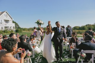 bride-and-groom-walk-up-flower-petal-aisleway-at-outdoor-ceremony