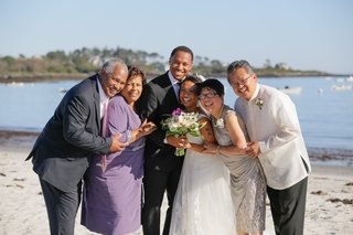 bride-and-groom-with-parents-on-beach-in-maine