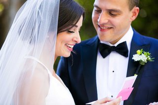 bride-opens-pink-letter-and-reads-it-in-front-of-her-groom-before-their-ceremony