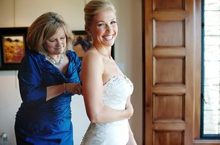 mother-of-bride-helps-daughter-into-wedding-dress