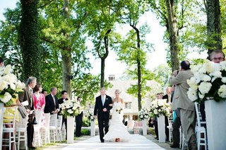 bride-walks-down-aisle-with-father-under-green-trees