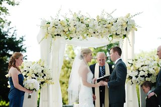 bride-and-groom-under-canopy-of-white-flowers