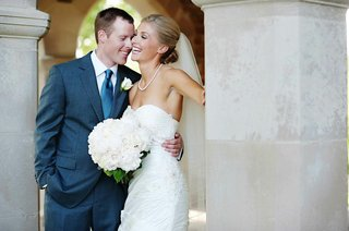 groom-in-navy-suit-with-bride-in-strapless-white-dress