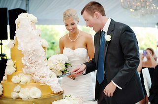 bride-and-groom-cut-into-gold-cake-with-white-sugar-flowers