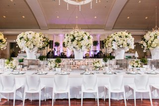 white-head-table-at-ballroom-wedding-with-white-chairs-white-tablecloth-white-centerpieces
