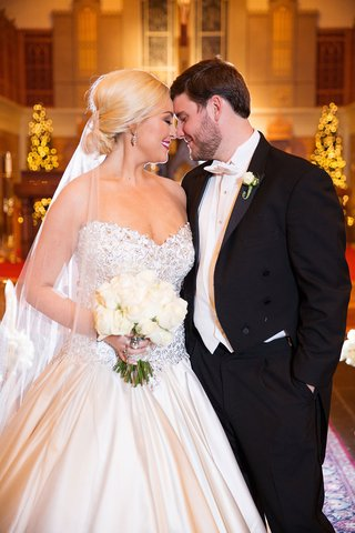 bride-in-strapless-pnina-tornai-wedding-dress-from-kleinfeld-bridal-with-white-bouquet-and-groom