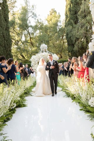 beverly-hills-hotel-wedding-bride-and-groom-walking-up-aisle-stock-and-ferns-along-aisle-white-arch