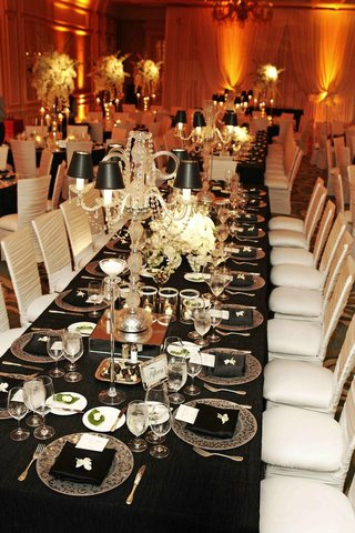 long-wedding-table-with-black-tablecloth-and-white-chairs