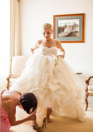 bridesmaid-helping-bride-put-shoes-on