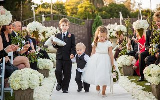 three-children-walk-down-petal-lined-aisle