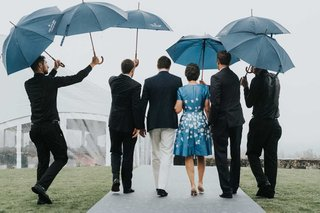 wedding-guests-walking-to-tented-ceremony-umbrellas-held-by-staff-mother-of-bride-in-blue-white-dres