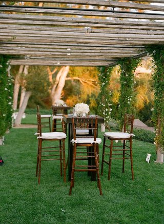 tall-cocktail-table-with-wood-chairs-and-white-flowers