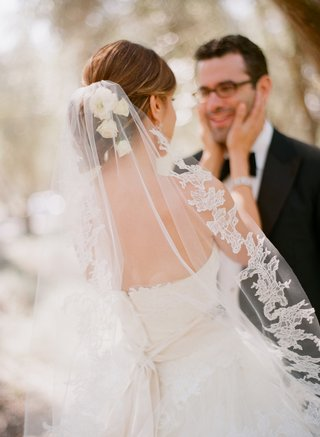 bride-touches-grooms-cheek-with-lace-bridal-veil
