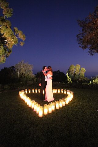 katherine-kallinis-and-groom-kiss-inside-heart-made-of-candles