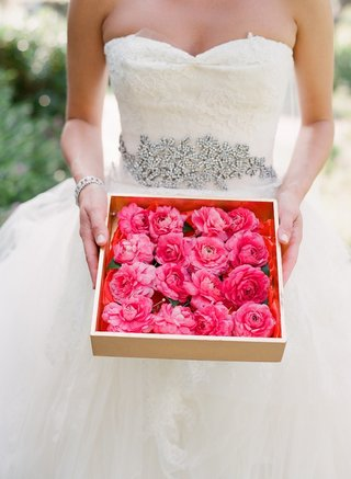 bride-holds-box-full-of-pink-flower-boutonniere