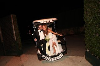 bride-and-groom-on-back-of-golf-cart-with-signage