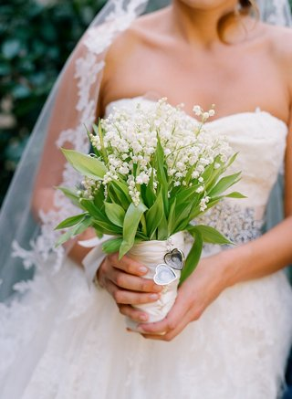 bride-holds-bouquet-of-lilies-of-the-valley-with-locket