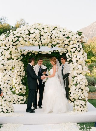 bride-and-groom-stand-under-white-flower-ceremony-structure