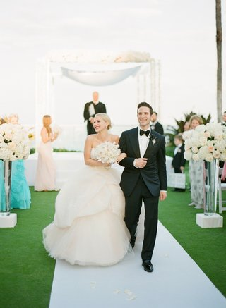 couple-walking-down-white-aisle-on-grass-lawn