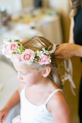 flower-girl-in-white-lace-dress-with-pink-rose-flower-crown-getting-hair-done-for-wedding