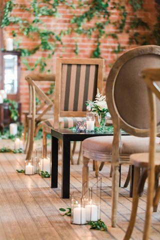 wedding-ceremony-wood-floors-brick-wall-with-greenery-wood-chairs-candles-greens
