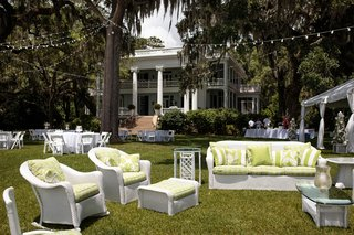 outdoor-lounge-area-with-white-wicker-furniture-and-green-pillows-and-cushions