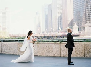 bride-sneaks-up-behind-groom-in-tuxedo-during-first-look-in-chicago