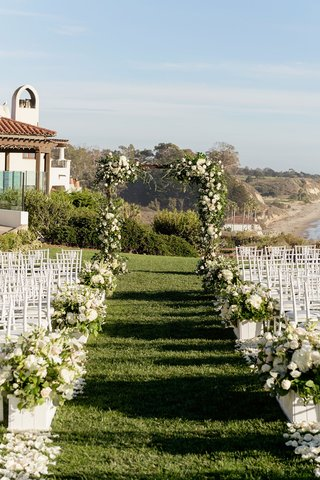 wedding-ceremony-green-grass-urns-boxes-filled-with-flowers-greenery-white-chairs-bacara-ocean-view