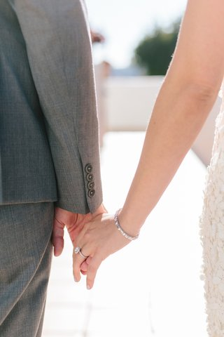 close-up-of-bride-and-groom-holding-hands-bride-wearing-diamond-tennis-bracelet-halo-engagement