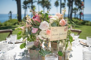 oceanfront-wedding-reception-table-with-white-peach-pink-roses-white-hydrangeas-red-protea