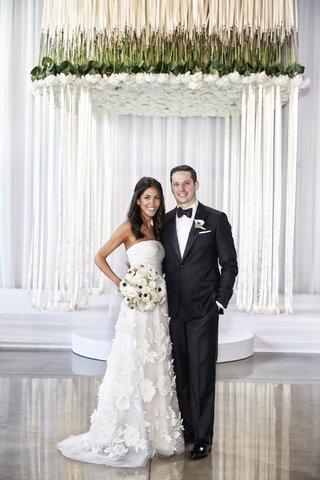 bride-in-oscar-de-la-renta-groom-in-j-hilburn-under-chuppah-of-flowers-and-ribbons