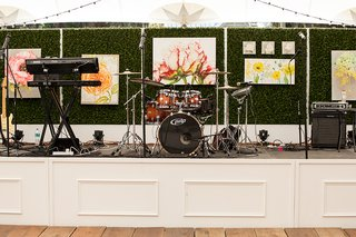 drum-set-keyboard-live-band-equipment-at-wedding-reception-on-stage-in-front-of-green-hedge-wall
