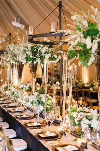 wedding-reception-long-table-leather-details-bronze-dark-wood-chandeliers-greenery-white-flowers