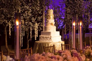 white-wedding-cake-with-two-golden-layers-fondant-petals-surrounded-by-cherry-blossom-trees