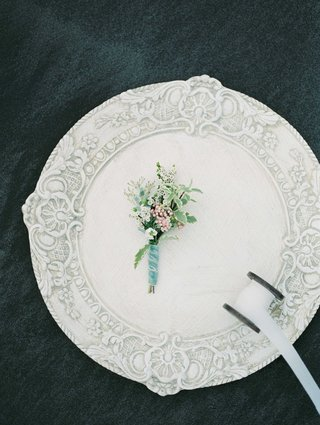 small-muted-boutonniere-with-green-foliage-and-white-flowers-on-a-white-charger-plate