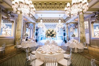 reception-centerpiece-with-white-peonies-and-hydrangeas-with-soft-greenery-on-tall-crystal-stansd