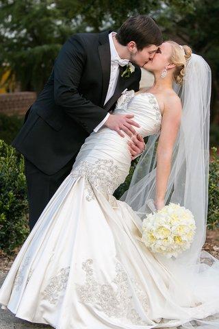 man-in-tuxedo-kissing-woman-in-wedding-dress