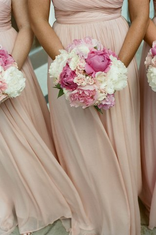 bridesmaids-in-pale-dresses-holding-peony-flowers