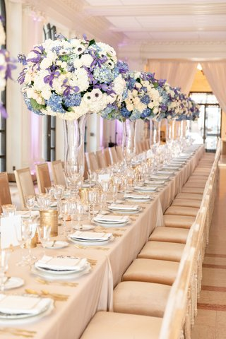 intimate-wedding-reception-with-tall-crystal-vases-floral-arrangements-with-blue-white-flowers